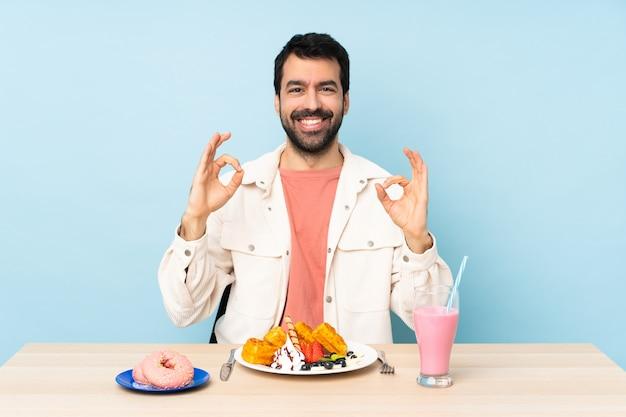 Mann an einem tisch, der frühstückswaffeln und einen milchshake zeigt ein okayzeichen mit den fingern isst