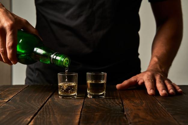 Mann an einer bar, die alkohol in schnapsgläsern trinkt. konzept von alkoholismus und alkoholabhängigkeit.