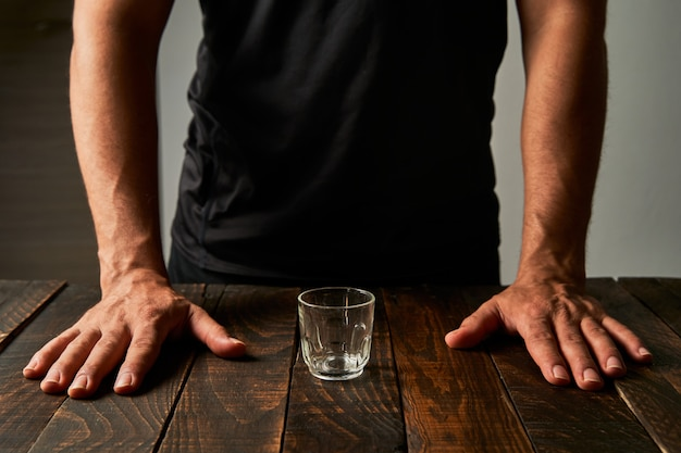 Mann an einer bar mit einem schnapsglas. konzept von alkoholismus und sucht.