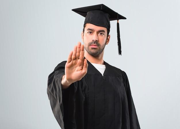 Mann an seinem abschlusstag, der universität macht, gestikulieren mit ihrer hand, die eine situation bestreitet