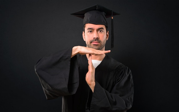 Mann an seinem abschlusstag, der universität macht, stoppen geste mit ihrer hand, um eine tat zu stoppen