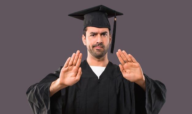 Mann an seinem abschlusstag universität macht stop geste mit ihrer hand für enttäuscht