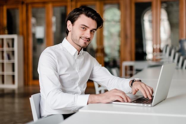 Mann an seinem arbeitsplatz mit laptop im büro