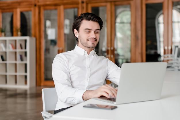 Mann an seinem arbeitsplatz mit telefon und laptop im büro