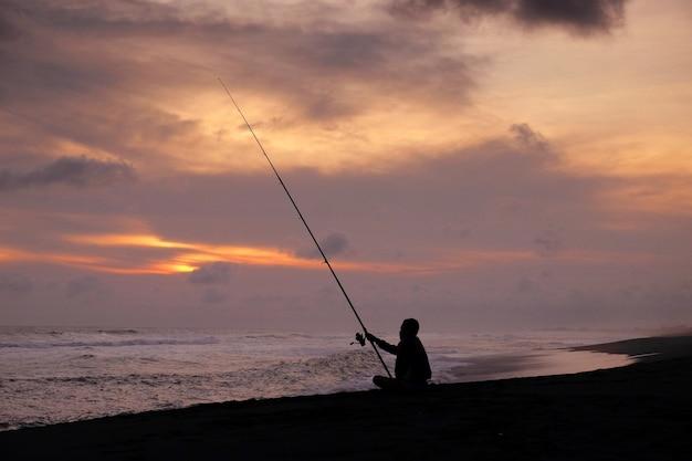Mann angeln am strand während des sommersonnenuntergangs