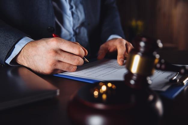 Mann anwalt, der mit papiervertrag arbeitet. holzhammer und waage auf dem schreibtisch.