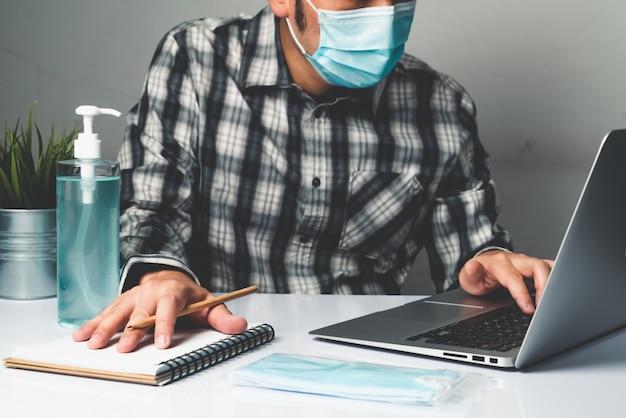 Mann arbeiten im büro zu hause, um vor coronavirus-krankheit oder covid-19 zu schützen.