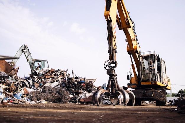 Mann arbeiter, der schrott-recycling-maschine im schrottplatz betreibt.