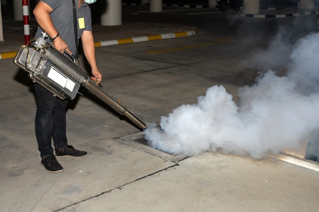 Mann arbeiter vernebelt insektizid, um mücken zu beseitigen, um dengue-fieber und zika-virus zu verhindern