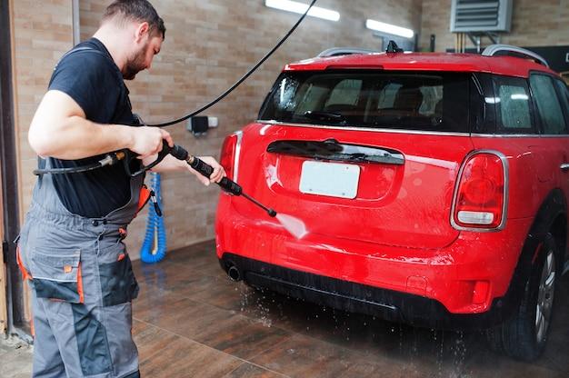Mann arbeiter waschen rotes auto in der detaillierung garage