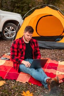 Mann arbeitet am laptop auf dem campingplatz im herbst herbstsaison. freiberufliches konzept