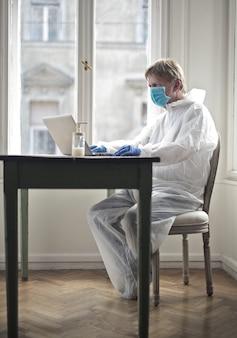 Mann arbeitet an einem computer, der durch einen medizinischen anzug und eine maske geschützt ist