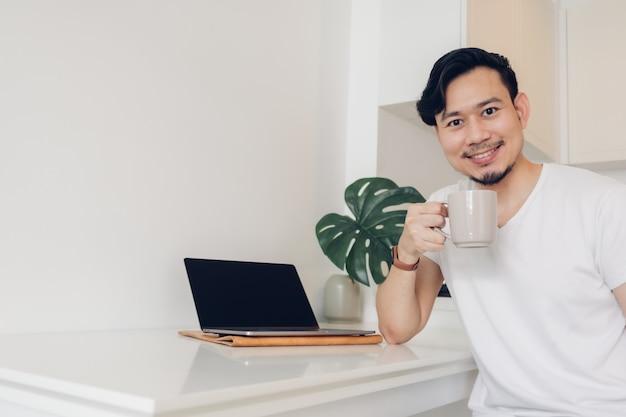 Mann arbeitet an seinem laptop auf weißem minimalem arbeitsbereich und grüner pflanze.