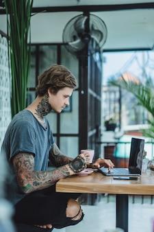Mann arbeitet in einem Café. Konzept von Freelancern, Kaffee und Laptop