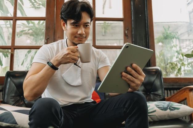 Mann arbeitet in einem wohnzimmer mit tablet- und kaffeekonzept von staycation