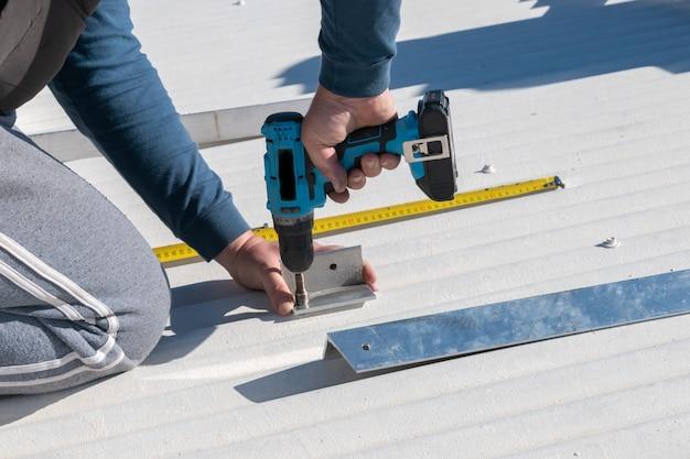 Mann arbeitet mit bohrer bei der installation von solarmodulen