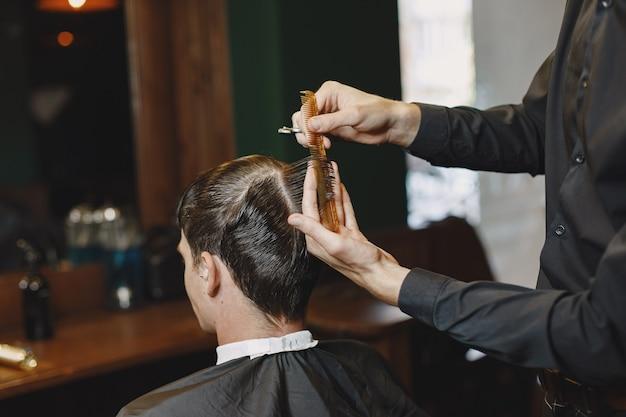 Mann arbeitet mit haaren. friseur mit einem kunden.