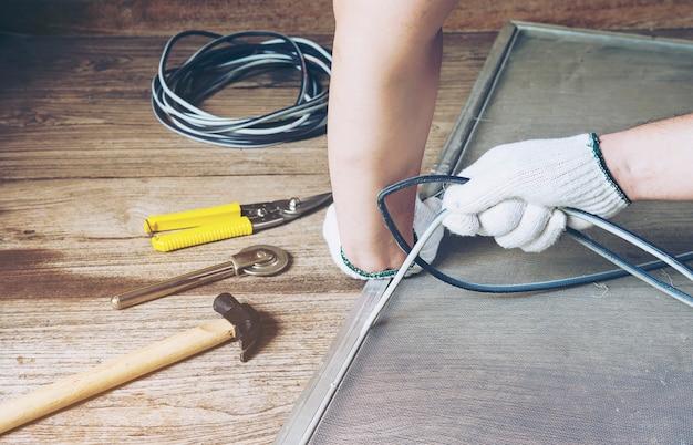 Mann arbeitet mit moskito-draht-bildschirminstallation