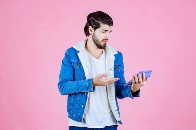 Mann arbeitet mit taschenrechner und sieht verwirrt aus