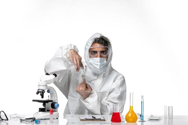 Mann arzt im schutzanzug und mit steriler maske, die leere flasche auf weiß hält