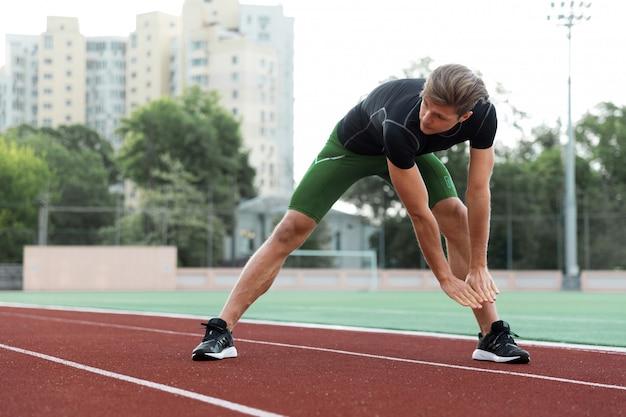 Mann athlet machen dehnübungen