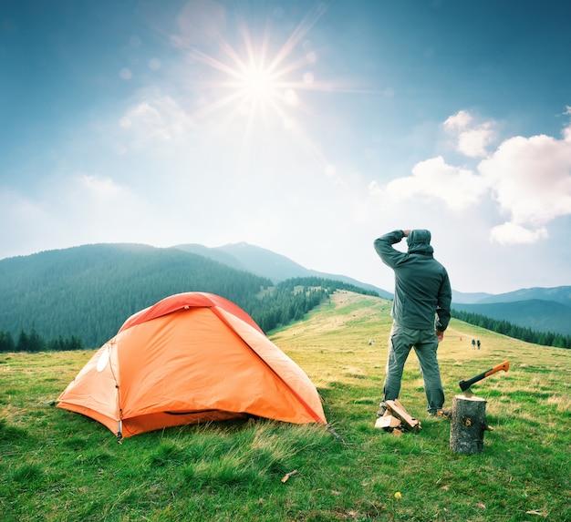 Mann auf berg nahe orange zelt schaut in die ferne