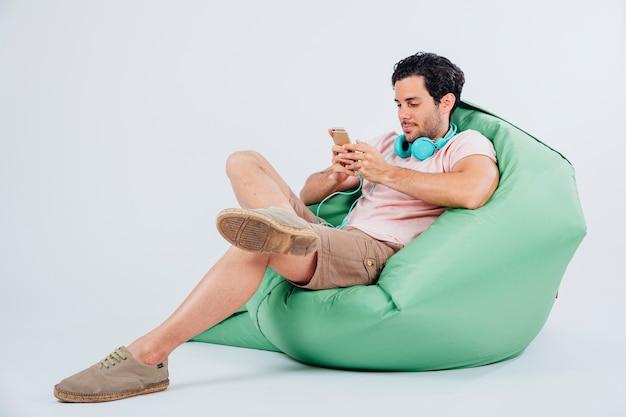 Mann auf couch eingabe auf smartphone