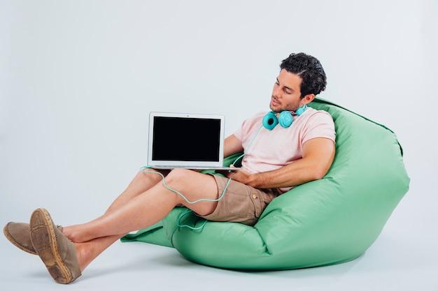 Mann auf couch präsentiert laptop