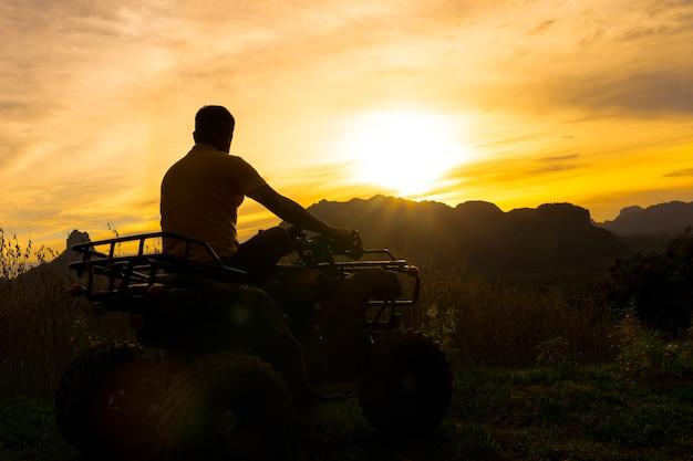 Mann auf dem atv auto, welches den sonnenuntergang über einem großen berg betrachtet. portrait eines sillhouette.