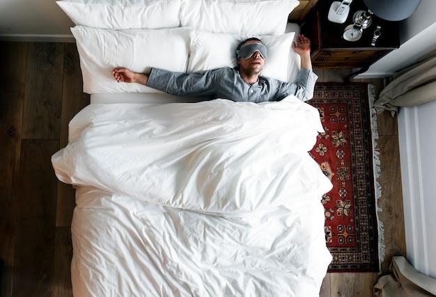 Mann auf dem bett schlafend mit einer augenabdeckung