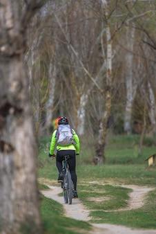 Mann auf dem fahrrad, das den weg eines waldes kreuzt