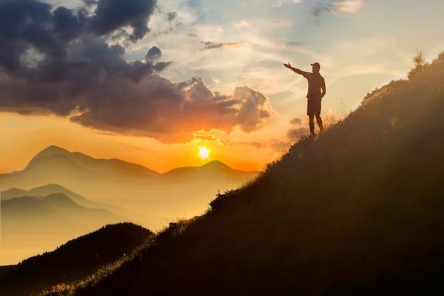 Mann auf dem gipfel des berges. emotionale szene. junger mann mit dem rucksack, der mit den angehobenen händen auf einen berg steht.