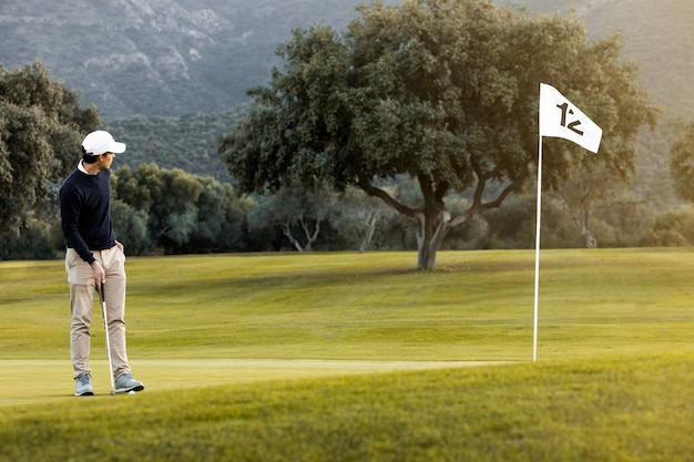 Mann auf dem golfplatz neben flagge