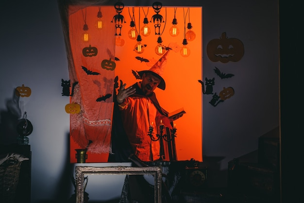 Mann auf dem horrorhintergrund. halloween-hexe mit einem geschnitzten kürbis und magischen lichtern in einem dunklen wald. halloween-party für glückliche familie. hexen hut. halloween party und lustiger kürbis