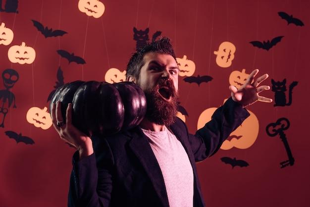 Mann auf dem horrorhintergrund halloween-hexe mit einem geschnitzten kürbis und magischen lichtern in einem dunklen wald...
