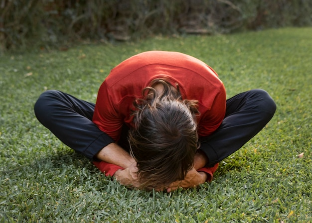 Mann auf dem rasen im freien, der yoga tut