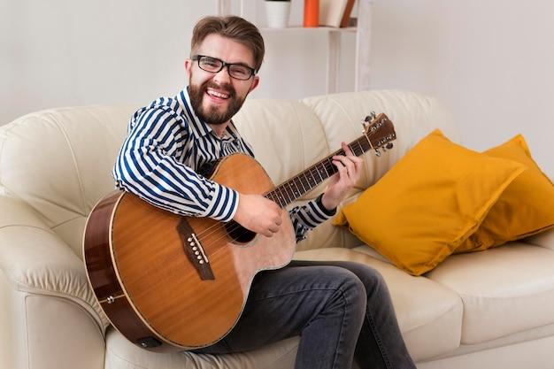 Mann auf dem sofa zu hause, das gitarre spielt