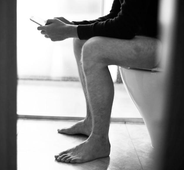 Mann auf dem toilettensitz mit einem smartphone