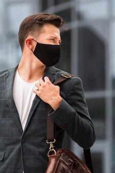 Mann auf dem weg zur arbeit während der pandemie mit gesichtsmaske