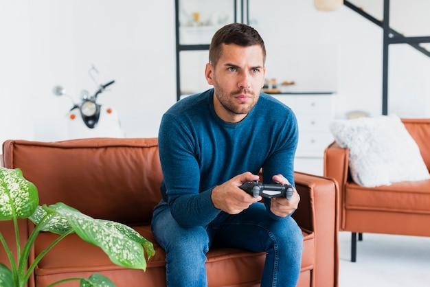 Mann auf der couch, die spiele mit steuerknüppel spielt