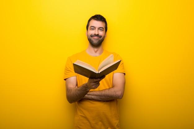 Mann auf der lokalisierten vibrierenden gelben farbe, die ein buch hält und es jemandem gibt
