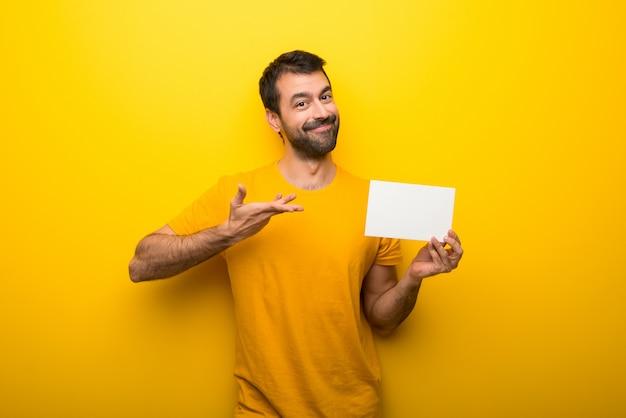 Mann auf der lokalisierten vibrierenden gelben farbe, die ein leeres weißes plakat für einfügen ein konzept hält