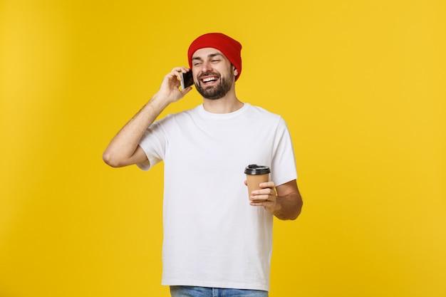 Mann auf der lokalisierten vibrierenden gelben farbe, die einen kaffee in der mitnehmerpapierschale nimmt und lächelt, weil er den tag gut beginnt.