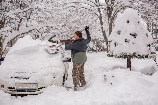 Mann auf der straße an einem wintertag räumt das auto von schnee
