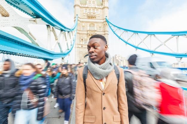 Mann auf der tower bridge, london, mit verschwommenen menschen