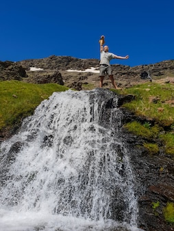 Mann auf einem berg auf einem wasserfall mit einer kettlebell