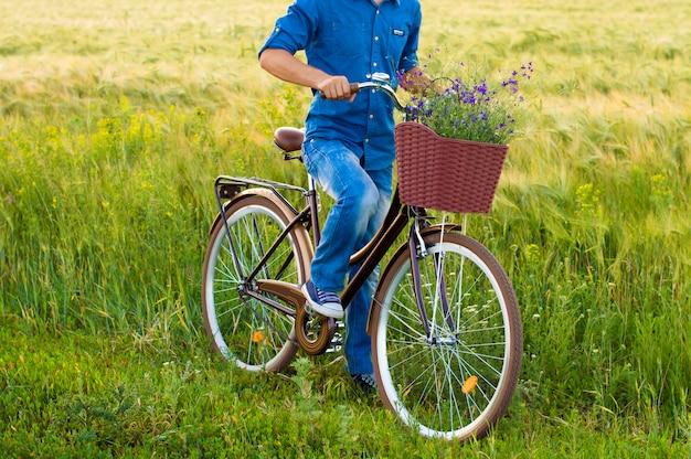 Mann auf einem fahrrad mit blumen in einem korb