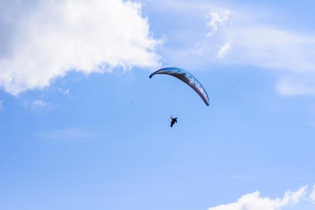 Mann auf einem fallschirm, der im klaren himmel fliegt