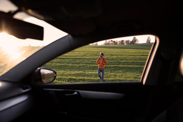 Mann auf einem straßenausflug im freien gesehen von der innenseite eines autos