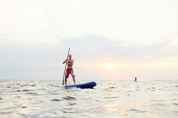 Mann auf einem sup-brett gegen einen schönen sonnenuntergang und das meer